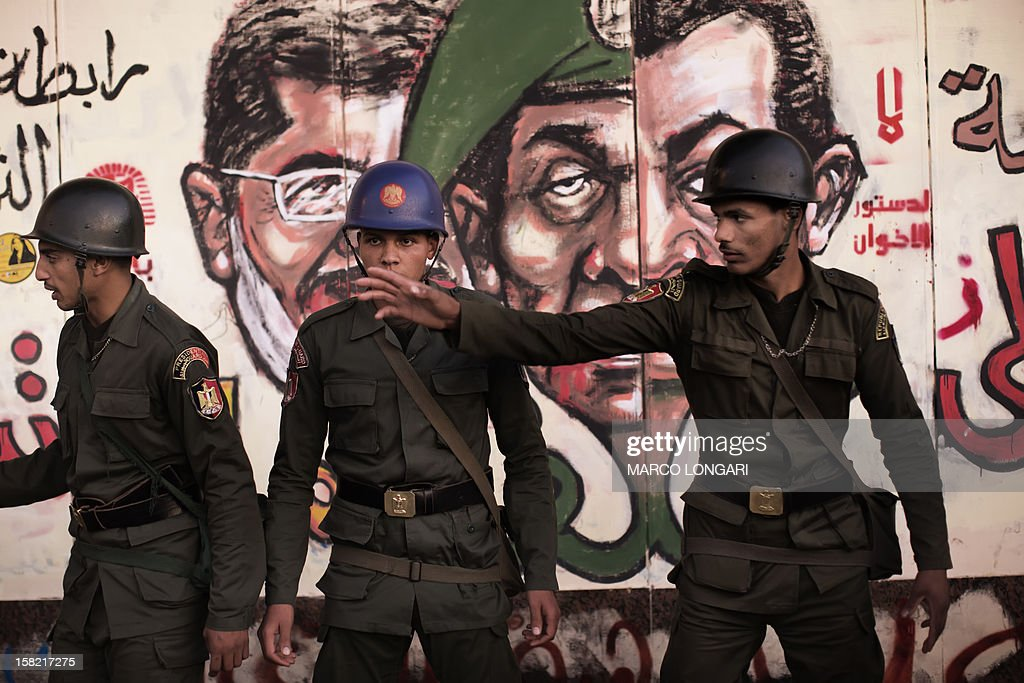 Egyptian soldiers stand in front of a graffiti on the walls of the Presidential Palace in Cairo on December 11, 2012 as thousands of Egyptian opposition supporters rally outside the site to protest against the upcoming referendum on the new draft constitution. Protesters gathered in Cairo for rival rallies over a deeply disputed constitutional referendum proposed by Egypt's Islamist president, Mohamed Morsi, raising fears of street clashes .
