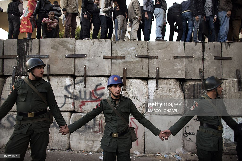 Egyptian soldiers stand in line as anti President Mohamed Morsi protesters stand on top of a barricade erected by the Egyptian army to protect the Presidential Palace in Cairo on December 11, 2012. Protesters gathered in Cairo for rival rallies over a deeply disputed constitutional referendum proposed by Egypt's Islamist president, Mohamed Morsi, raising fears of street clashes .