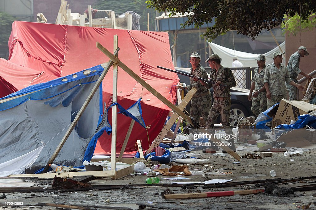 Egyptian soldiers walk amid the remains of the destroyed camp of ousted Mohammed Morsi supporters outside Rabaa alAdawiya mosque on August 15 2013 in...