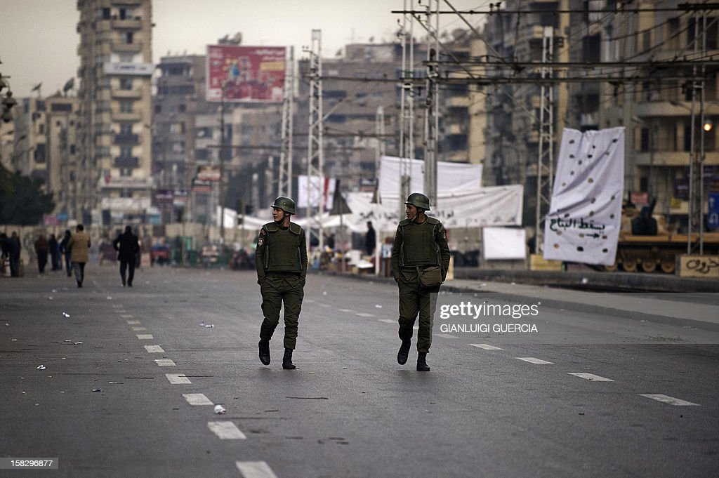 Egyptian soldiers walk through a street near the presidential palace in Cairo on December 13, 2012. Egypt's crisis showed no sign of easing as the army delayed unity talks meant to ease political divisions and the opposition set near-impossible demands for taking part in a looming constitutional referendum. AFP PHOTO/GIANLUIGI GUERCIA