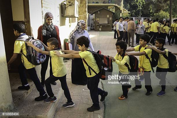 Egyptian students go to their classroom after singing their national anthem as Egyptian Education Minister AlHilali Al Sherbini arrives to inspect...