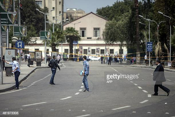 Egyptian students pass in front of a cordonned off area after twin bombs struck police posts near Cairo University in the centre of Egypt's capital...