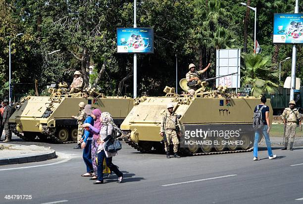 Egyptian students walk past soldiers standing guard in armored personnel carriers in the street in front of Cairo University during clashes following...