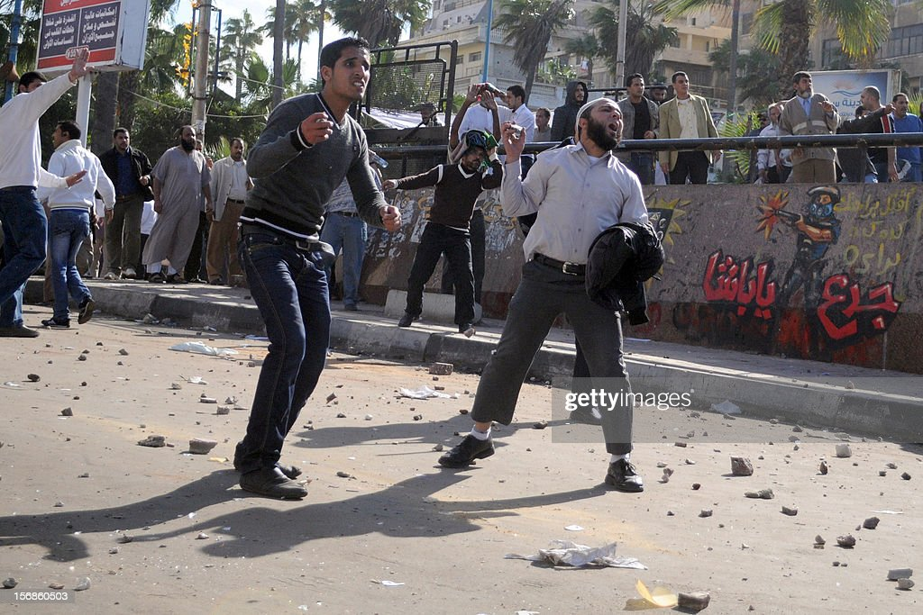 Egyptian supporters and opponents of President Mohamed Morsi clash in the Mediterranean coastal city of Alexandria on November 23, 2012. Opponents set fire to Muslim Brotherhood offices in three Egyptian cities, state television reported, as rival rallies gathered nationwide a day after Morsi assumed sweeping powers. AFP PHOTO / STR