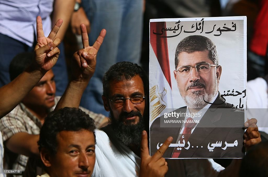 Egyptian supporters of deposed president Mohamed Morsi flash the sign of victory showing his portrait during a rally outside Cairo's Rabaa al-Adawiya mosque late June 10, 2013. Egypt's Prime Minister said on July 11 that he does not rule out posts for the Muslim Brotherhood in his cabinet if candidates are qualified, even as police cracked down on Morsi's Islamist group.