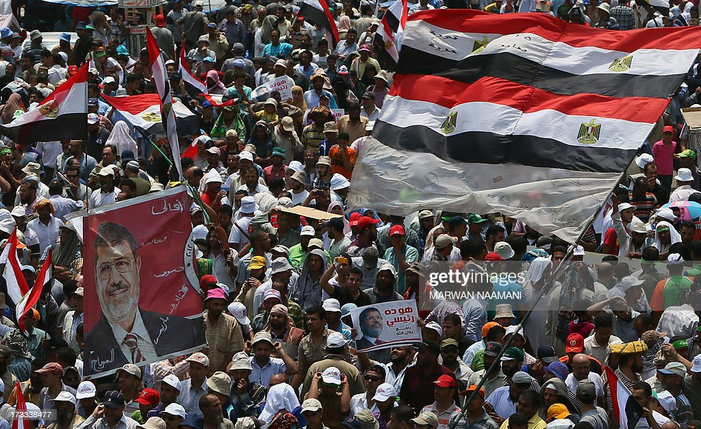 Egyptian supporters of the Muslim Brotherhood and deposed president Mohamed Morsi (on poster) wave a giant national flag during a rally outside Cairo's Rabaa al-Adawiya mosque on July 12, 2013, following Friday noon prayer. Activists for and against ousted Morsi have called rival rallies for the first Friday of Ramadan, as tensions soar over the army's overthrow of the Islamist leader.
