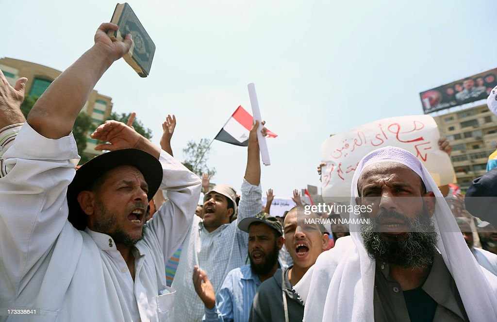 Egyptian supporters of the Muslim Brotherhood and deposed president Mohamed Morsi shout slogans, one raising up a Koran, during a rally outside Cairo's Rabaa al-Adawiya mosque on July 12, 2013, following Friday noon prayer. Activists for and against ousted Morsi have called rival rallies for the first Friday of Ramadan, as tensions soar over the army's overthrow of the Islamist leader.