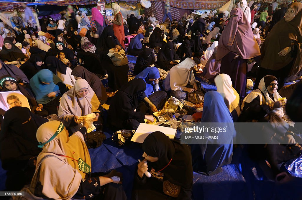 Egyptian supporters of the Muslim Brotherhood and Egypt's ousted president Mohamed Morsi break the fast outside Cairo's Rabaa al-Adawiya mosque on July 10, 2013, the first day of Islam's holy month of Ramadan. Tens of millions across the Muslim world fast from dawn to dusk and strive to be more pious and charitable during the month, which ends with the eid holiday. AFP PHOTO / MAHMUD HAMS