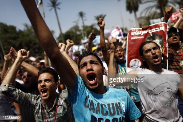 Egyptian supporters of the Muslim Brotherhood and ousted president Mohamed Morsi shout religious and political slogans during a protest near Cairo...
