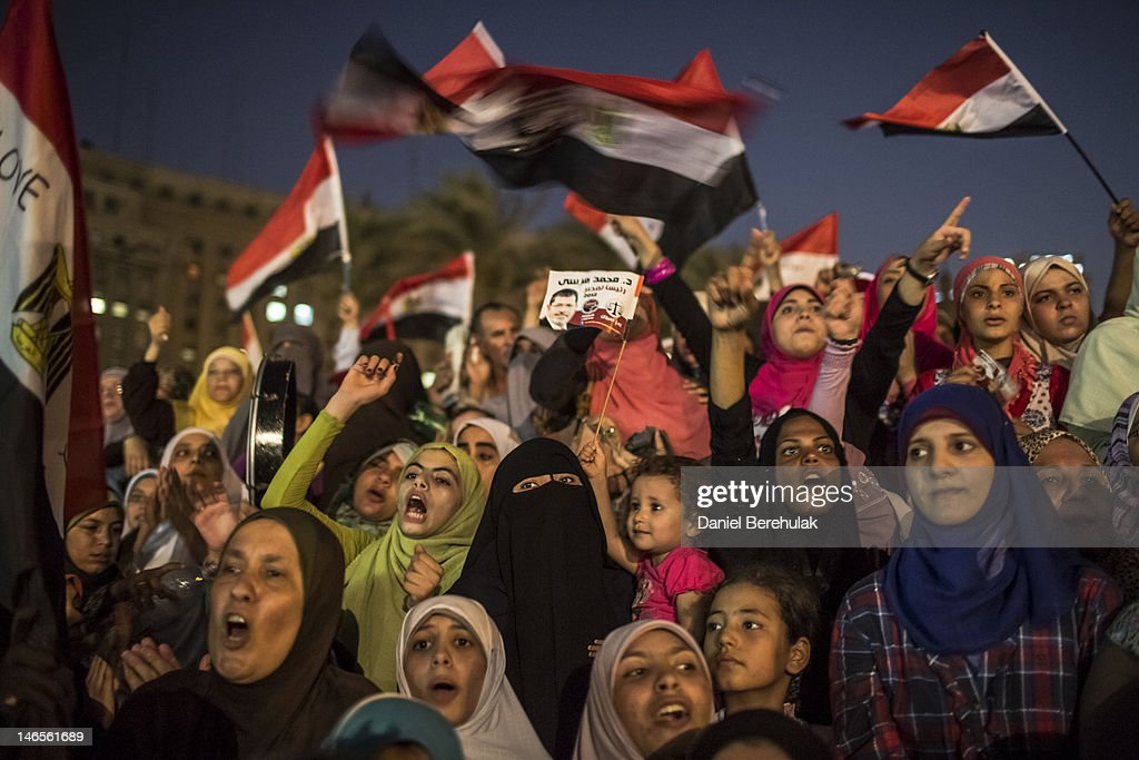 Egyptian supporters of the Muslim Brotherhood react to speeches at a gathering to celebrate a premature victory for their presidential candidate...