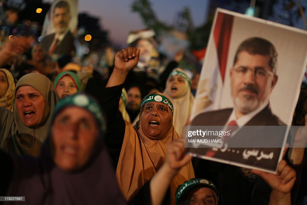 Egyptian supporters of the Muslim Brotherhood shout slogans in favour of Egypt's deposed president Mohamed Morsi (portrait) after breaking the fast outside Cairo's Rabaa al-Adawiya mosque on July 10, 2013, the first day of Islam's holy month of Ramadan. Tens of millions across the Muslim world fast from dawn to dusk and strive to be more pious and charitable during the month, which ends with the eid holiday.