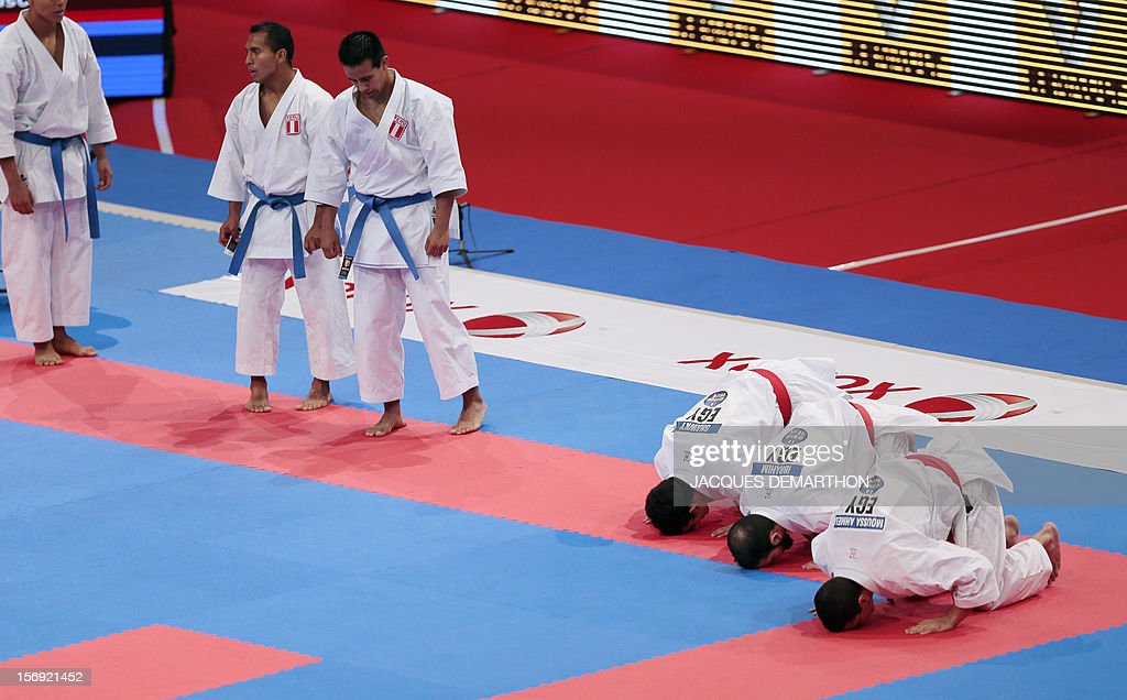 Egyptian team members (R) pray to celebrate their victory over the Peruvian team (L) on November 25, 2012 in the men's team kata semi-finals of the Karate world championships at the POPB stadium in Paris. DEMARTHON