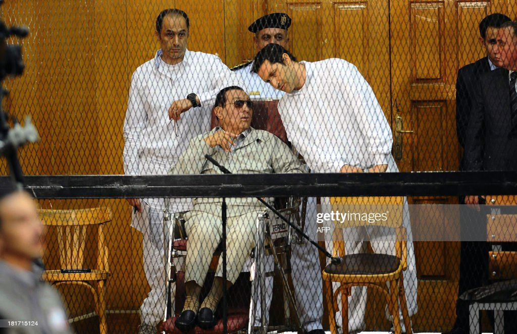 Egyptian toppled president <a gi-track='captionPersonalityLinkClicked' href=/galleries/search?phrase=Hosni+Mubarak&family=editorial&specificpeople=201752 ng-click='$event.stopPropagation()'>Hosni Mubarak</a> and his two sons Alaa (R) and Gamal stand behind bars during their trial at the Police Academy on September 14, 2013 in Cairo. Mubarak appears in court for the second time since his release from Cairo's Tora prison and he faces an array of charges, including complicity in the deaths of some 850 people killed in the Arab Spring-inspired uprising against him, and corruption. AFP PHOTO / AHMED EL-MALKY
