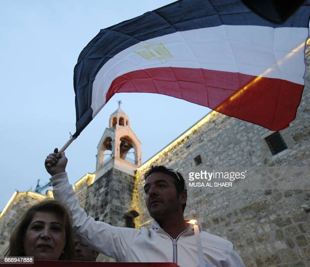 Egyptian tourists wave their country's national flag during a gathering in the West Bank town of Bethlehem on April 10 2017 in solidarity with the...