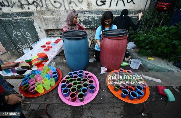 Egyptian volunteers distribute free juice in the street in Cairo during the Muslim holy fasting month of Ramadan on June 22 2015 AFP PHOTO / MOHAMED...