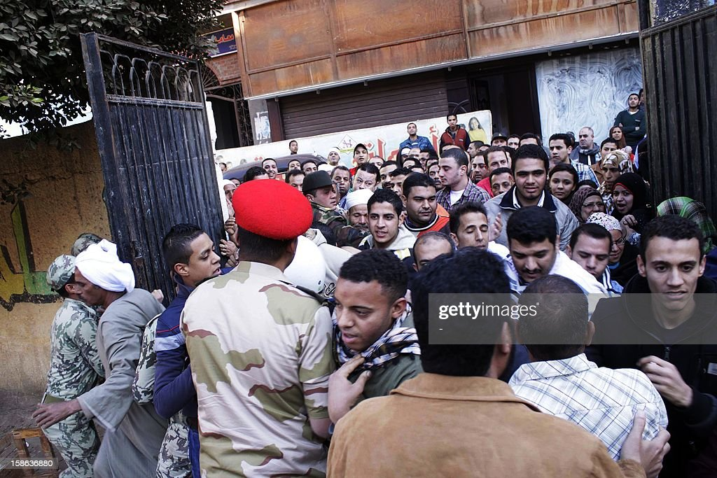 Egyptian voters scuffle with army soldiers as they enter a polling station in Giza, south of Cairo, on December 22, 2012. Egyptians voted in the final round of a referendum on a new constitution championed by President Mohamed Morsi and his Islamist allies, but with little prospect of the result quelling fierce protests. AFP PHOTO/STR
