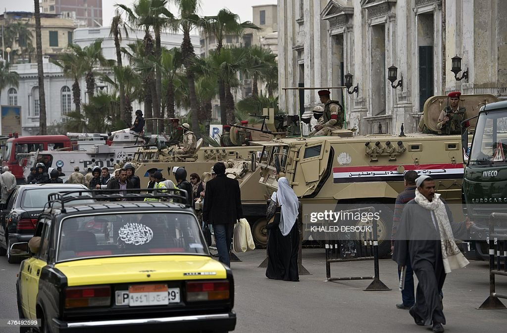 Egyptian walk past Egyptian soldiers guarding with armoured personnel carriers (APC) outside the criminal court in Egypt's Mediterranean city of Alexandria on March 3, 2014, during the retrial of the two policemen Awad Ismail Suleiman and Mahmoud Salah Mahoud, who are accused of using excessive force and killing 28-year-old blogger Khaled Said. The two policemen were sentenced to ten years in jail for the killing of the blogger whose death rallied protesters in the 2011 revolt that toppled Hosni Mubarak.