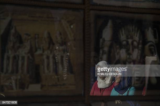 Egyptian women are seen reflected on pharaonic images displayed outside a shop in Cairo on July 14 2016 Many believed that Mohamed Morsi's ouster...
