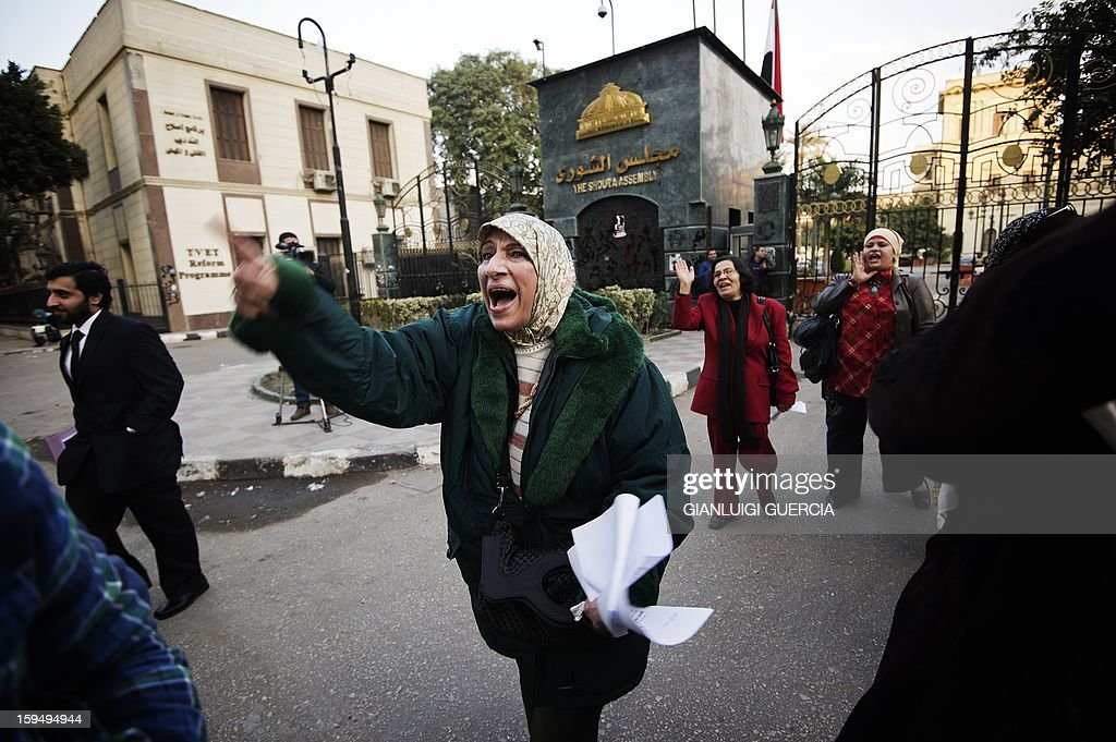 Egyptian women chase away people leaving the Egyptian Shura Assembly building as they demonstrate demanding more rights for minority groups and against the new election law, on January 14, 2013 in Cairo. Egypt is due to hold parliamentary elections, possibly in March or April.