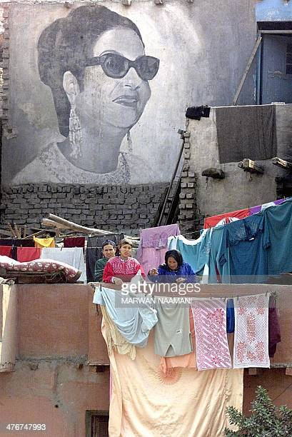 Egyptian women collects clothes in front of a giant picture of Egyptian diva Umm Kulthum painted on a shack in the Kom alGhurab suburb of Cairo 02...
