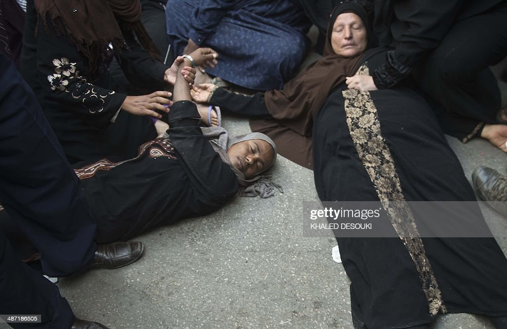 Egyptian women faint outside the courtroom in Egypt's central city of Minya after an Egyptian court sentenced Muslim Brotherhood leader Mohamed Badie and other alleged Islamists to death on April 28, 2014. The defendants were accused of involvement in the murder and attempted murder of policemen in Minya province on August 14, the day police killed hundreds of ousted Islamist president Mohamed Morsi's supporters in clashes in Cairo.