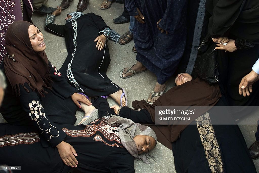 Egyptian women faint outside the courtroom in Egypt's central city of Minya after an Egyptian court sentenced Muslim Brotherhood leader Mohamed Badie and other alleged Islamists to death on April 28, 2014. The defendants were accused of involvement in the murder and attempted murder of policemen in Minya province on August 14, the day police killed hundreds of ousted Islamist president Mohamed Morsi's supporters in clashes in Cairo. AFP PHOTO / KHALED DESOUKI