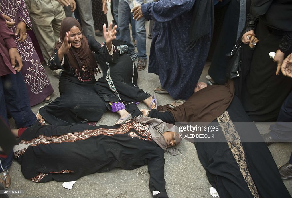 Egyptian women faint outside the courtroom in Egypt's southern province of Minya after an Egyptian court sentenced Muslim Brotherhood leader Mohamed Badie and other alleged Islamists to death on April 28, 2014. The defendants were accused of involvement in the murder and attempted murder of policemen in Minya province on August 14, the day police killed hundreds of ousted Islamist president Mohamed Morsi's supporters in clashes in Cairo.