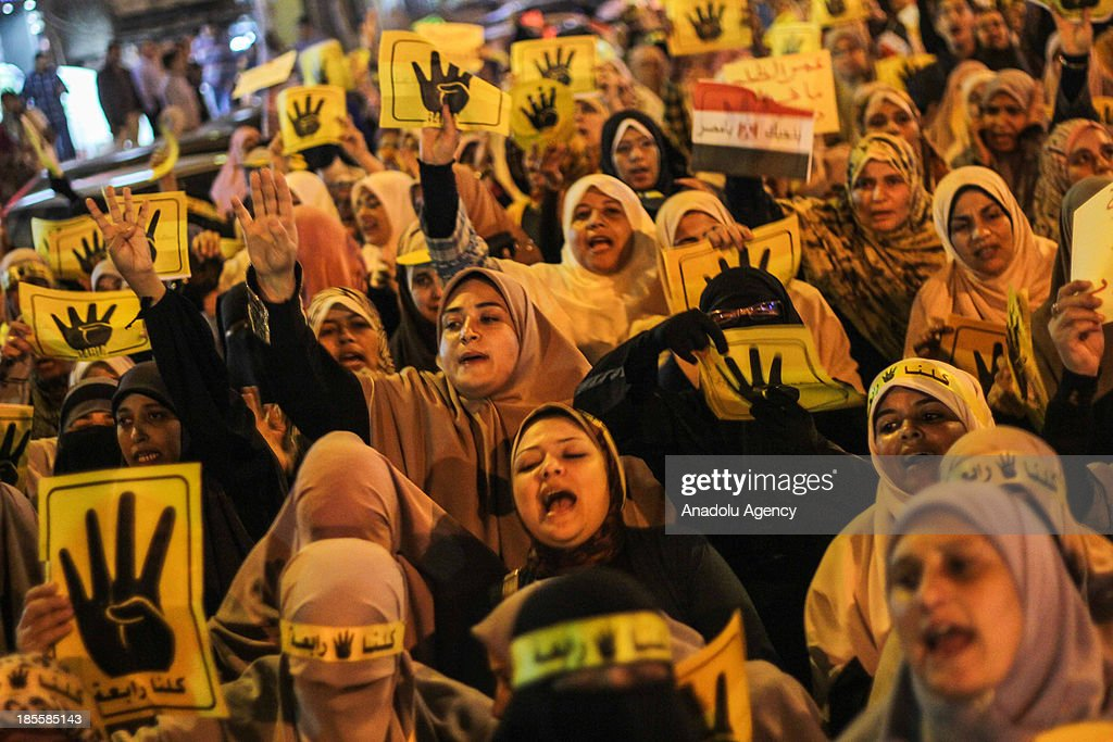 Egyptian women flash Rabia sign and shout slogans during an anti-coup rally on October 22, 2013 in the Sidi Bishr neighborhood of Alexandria, Egypt.
