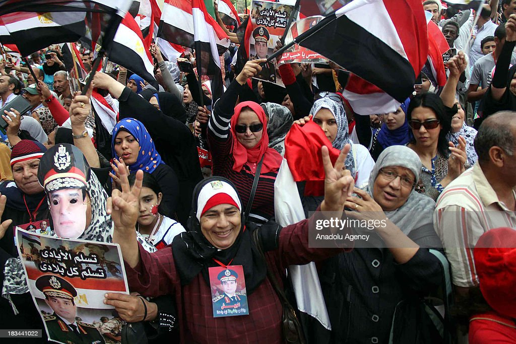 Egyptian women flash V-sign and wave national flags during the celebration marking the 40th anniversary of the 1973 victory over Israel in Tahrir Square on October 6, 2013 in Cairo, Egypt. Egypt celebrates the 40th anniversary of the 6th of October War victory against Israel for regaining the Sinai Peninsula.