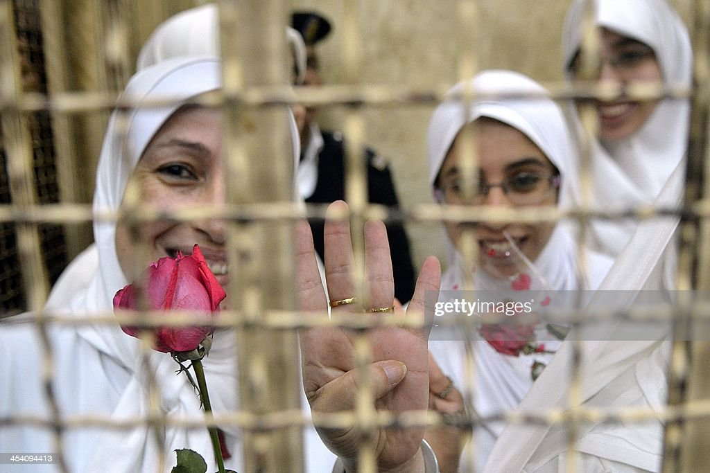 Egyptian women members of the Muslim Brotherhood hold roses and show a four-finger sign, called Rabaa (four) in Arabic as they stand in the defendants' cage during their trial in at the court in the Egyptian Mediterranean city of Alexandria on December 7, 2013. Egyptian judges began hearing appeals of 21 women and girls handed heavy jail terms over an Islamist protest, in a case that sparked an outcry. The 14 adult women were handed 11-year jail terms and the seven minors sentenced to juvenile detention last month, shocking even supporters of the military-installed government.