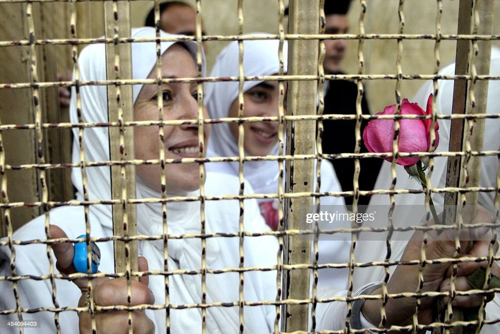 Egyptian women members of the Muslim Brotherhood hold roses as they stand in the defendants' cage dressed in prison issue white during their trial in at the court in the Egyptian Mediterranean city of Alexandria on December 7, 2013. Egyptian judges began hearing appeals of 21 women and girls handed heavy jail terms over an Islamist protest, in a case that sparked an outcry. The 14 adult women were handed 11-year jail terms and the seven minors sentenced to juvenile detention last month, shocking even supporters of the military-installed government.