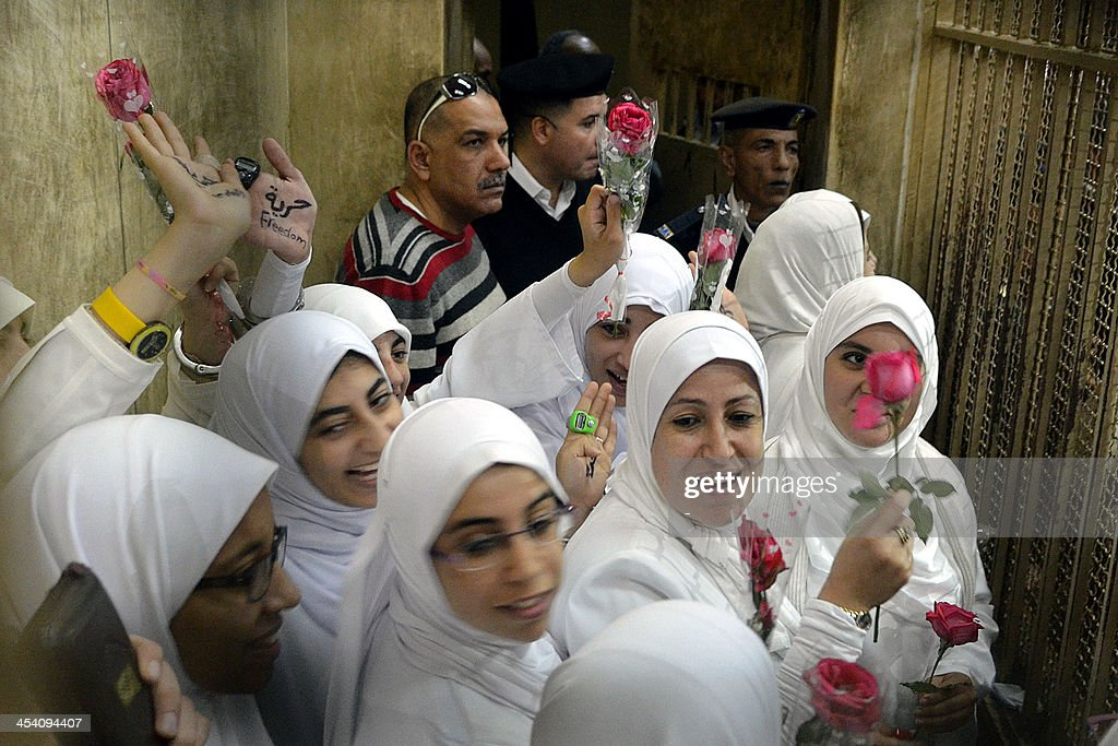 Egyptian women members of the Muslim Brotherhood hold roses as they stand in the defendants' cage dressed in prison issue white during their trial in at the court in the Egyptian Mediterranean city of Alexandria on December 7, 2013. Egyptian judges began hearing appeals of 21 women and girls handed heavy jail terms over an Islamist protest, in a case that sparked an outcry. The 14 adult women were handed 11-year jail terms and the seven minors sentenced to juvenile detention last month, shocking even supporters of the military-installed government. AFP PHOTO/STR