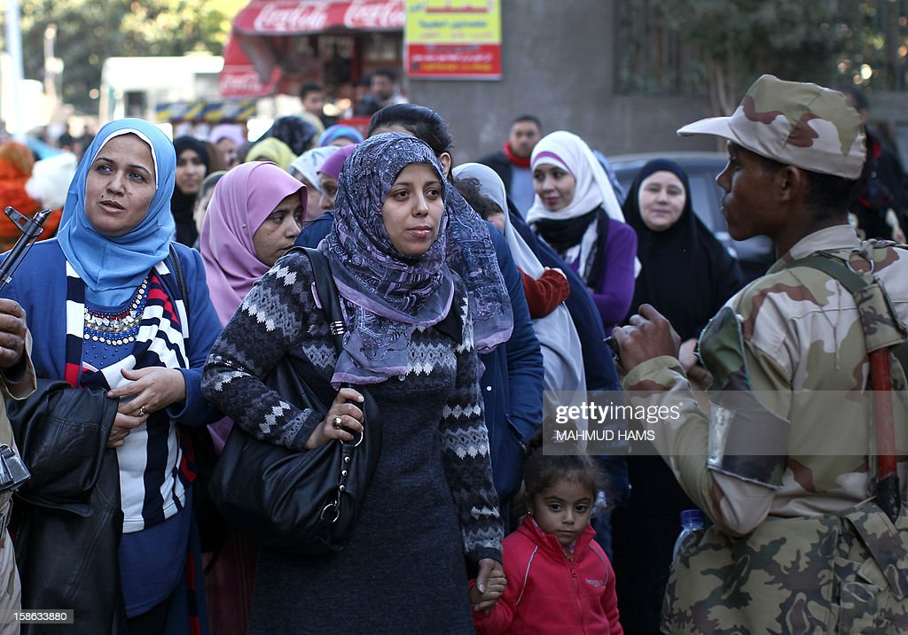 Egyptian women queue outside a polling station during the second round of a referendum on a new draft constitution in Giza, south of Cairo, on December 22, 2012. Egyptians are voting in the final round of a referendum on a new constitution championed by President Mohamed Morsi and his Islamist allies against fierce protests from the secular-leaning opposition. AFP PHOTO/MAHMUD HAMS