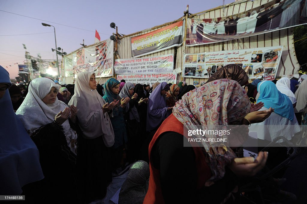 Egyptian women supporters of deposed president Mohamed Morsi perform the evening prayer in Cairo on July 26, 2013, as they continue to hold a sit-in outside Rabaa al-Adawiya mosque. Tense Egypt braced for a showdown in the streets between supporters of Morsi and his army-backed opponents, who have called for rival rallies across the Arab world's most populous country. AFP PHOTO / FAYEZ NURELDINE