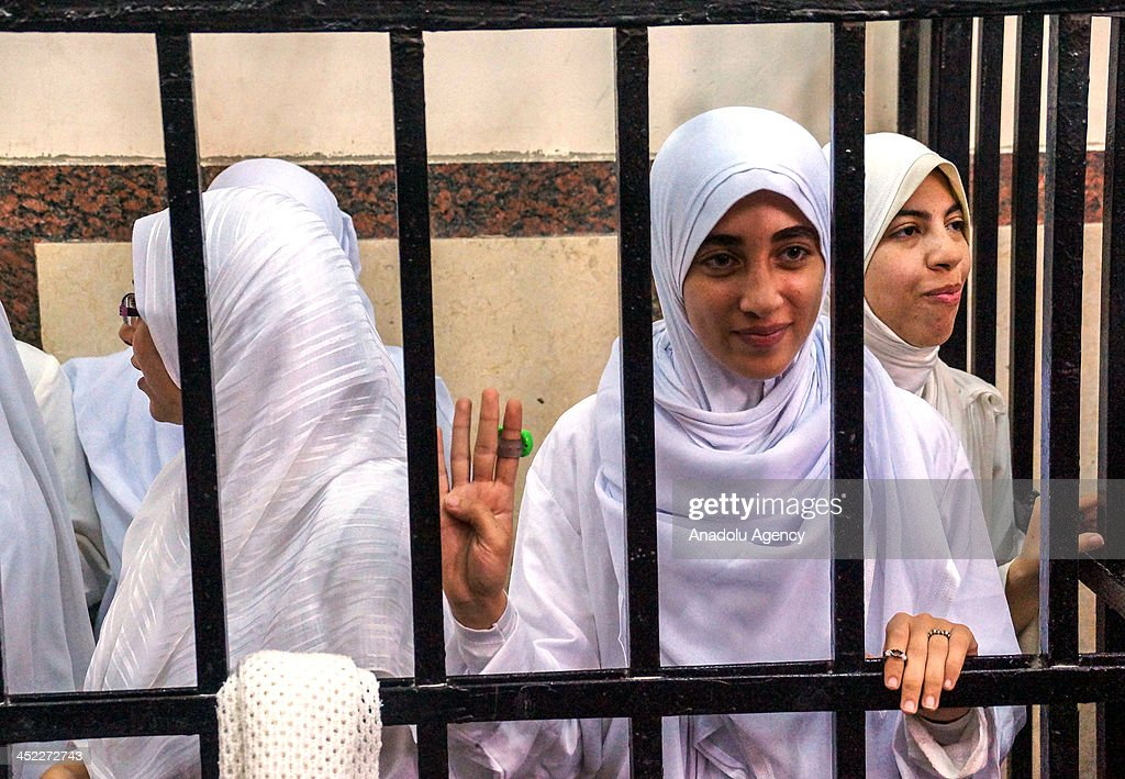 Egyptian women supporters of Mohammed Morsi stand in the courtroom in Alexandria, Egypt on November 27, 2013. An Egyptian court on Wednesday sentenced 14 female supporters of Mohamed Morsi to 11 years in prison each for illegal assembly.