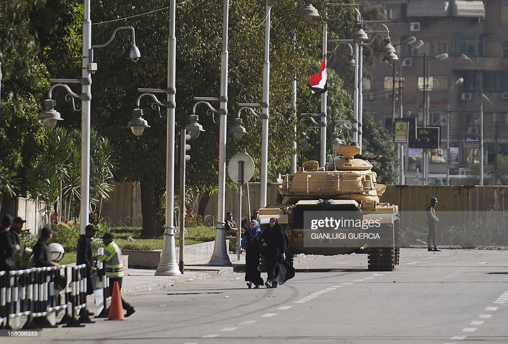Egyptian women walk in front of an armoured personnel carrier (APC) flying their national flag deployed near the presidential palace in Cairo on December 10, 2012. President Mohamed Morsi has ordered Egypt's army to 'cooperate' with police and given it powers of arrest until the results of a referendum to be held this weekend, according to a decree obtained by AFP.