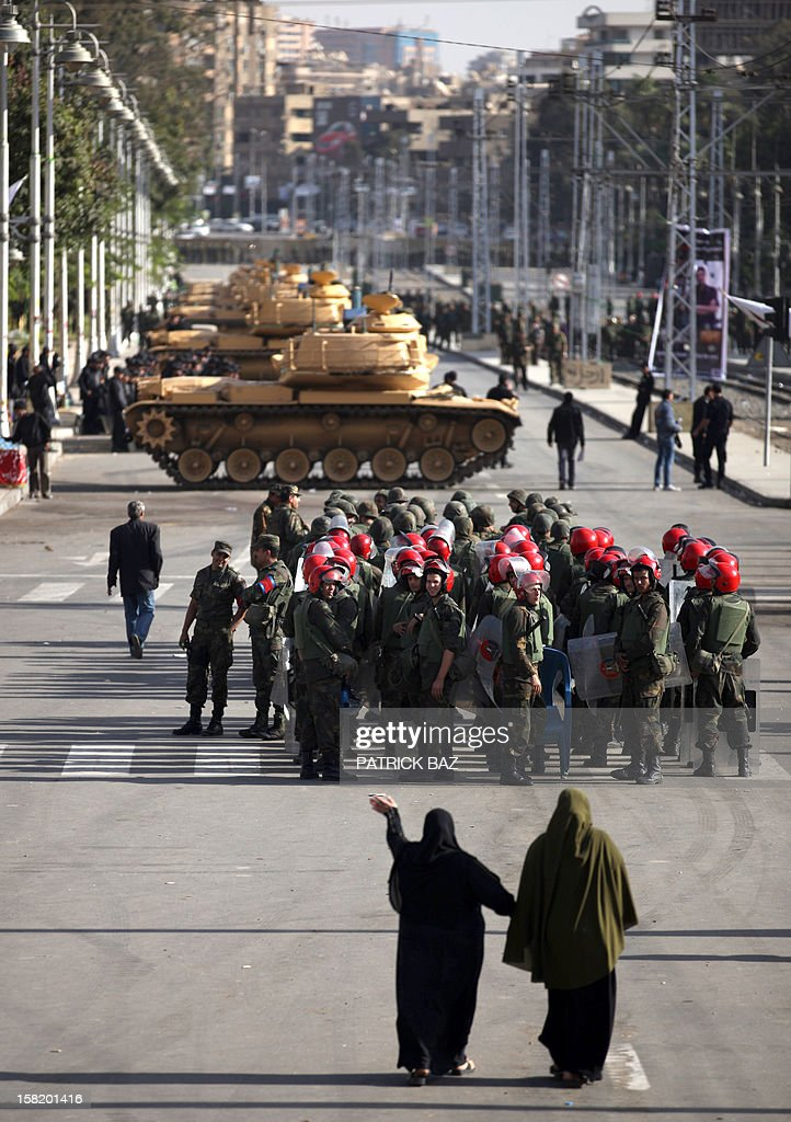 Egyptian women walk past tanks belonging to the Republican Guard and members of the military police deploying outside the presidential palace in Cairo on December 11, 2012. Protesters started to gather in the Egyptian capital for rival rallies for and against a divisive constitutional referendum proposed by President Mohamed Morsi. AFP PHOTO/PATRICK BAZ