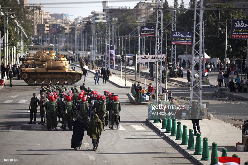 Egyptian women walk past tanks belonging to the Republican Guard and members of the military police deploying outisde the presidential palace in Cairo on December 11, 2012.. Protesters started to gather in the Egyptian capital for rival rallies for and against a divisive constitutional referendum proposed by President Mohamed Morsi. AFP PHOTO/PATRICK BAZ