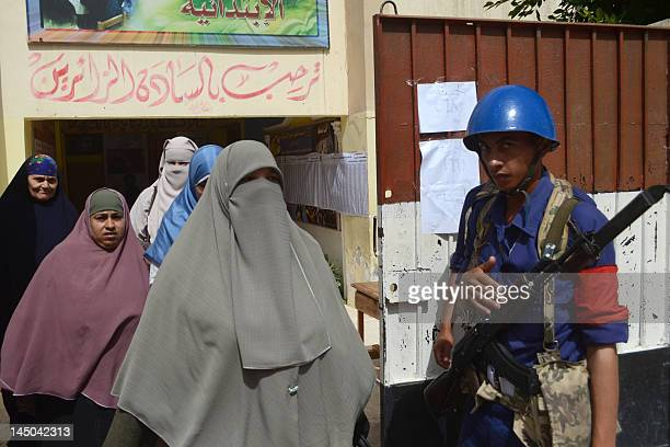 Egyptian women wearing Islamic coverings walk past a policeman as they exit polling station in the Egyptian coastal city of Alexandria on May 23...