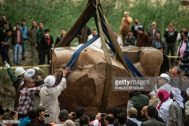 Egyptian workers excavate the statue recently discovered by a team of GermanEgyptian archeologists in Cairo's Mattarya district on March 13 2017...