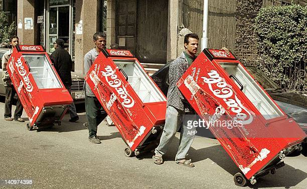 Egyptian workers push Coca Cola refrigerators through a Cairo street 29 February 2000 that are provided free of charge to kiosks and grocers selling...