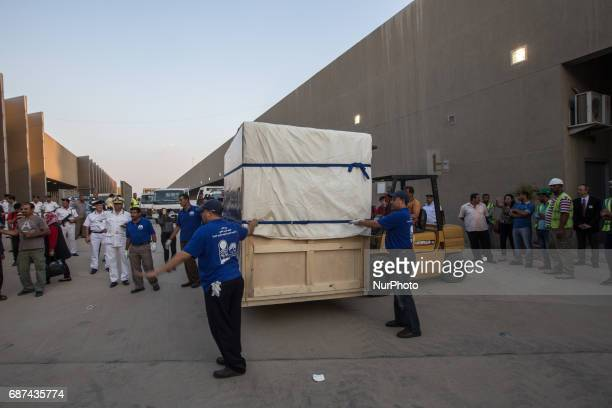 Egyptian workers transport a wooden crate with King Tutankhamun's funerary bed upon its arrival at the the restoration laboratory of the Grand...