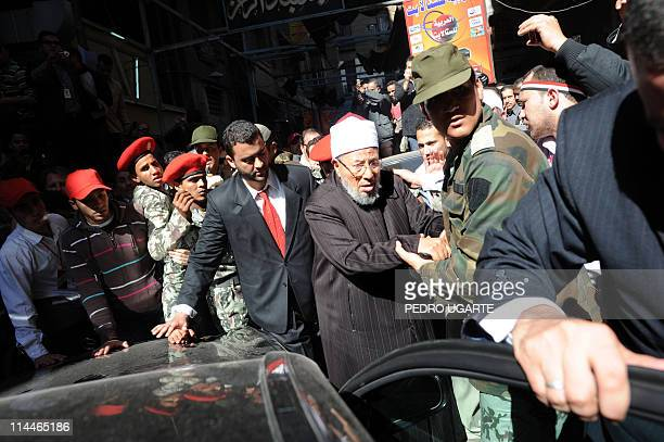 Egyptianborn Muslim cleric Sheikh Yussef alQaradawi is escorted by security as he leaves Cairo's central Tahrir square on February 18 2011 where he...