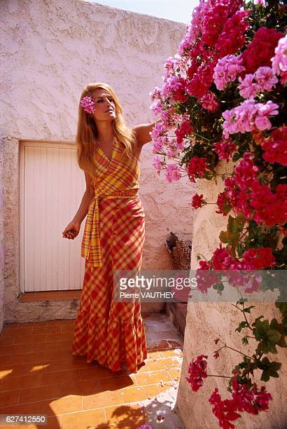 Egyptianborn singer Dalida picks red and pink flowers while vacationing in PortoVecchio Corsica