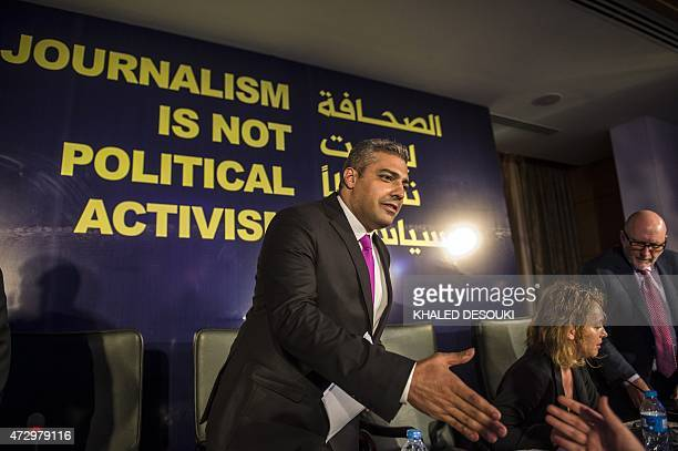 EgyptianCanadian journalist Mohamed Fahmy formerly with AlJazeera is greeted by an unknown man duting a press conference in Cairo on May 11 2015...