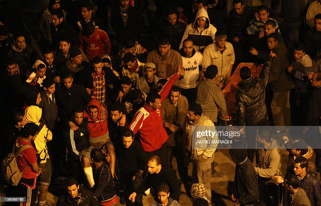 Egyptians carry a wounded AlAhly fan outside the train station in Cairo as they greet people who were wounded in clashes after a football match in...