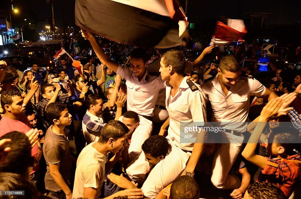 Egyptians carry police officers on their shoulders after a broadcast confirming the army will temporarily be taking over from the country's first...