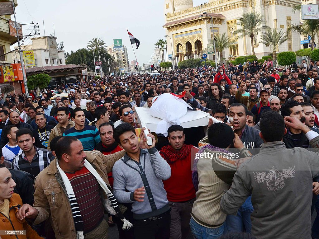 Egyptians carry the body of a person killed in overnight clashes between police and protesters in Egypt's Nile Delta city of Mansura, on March 2, 2013. Mansura is the latest province to launch a campaign of civil disobedience, following in the footsteps of the canal cities of Port Said, Ismailiya and Suez.