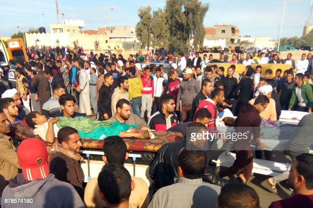 TOPSHOT Egyptians carry victims on stretchers following a gun and bombing attack on the Rawda mosque near the North Sinai provincial capital of...