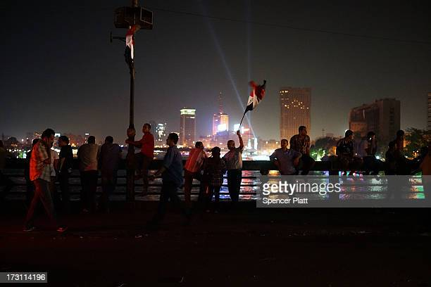 Egyptians celebrate into the night on a bridge near Tahrir Square following a massive rally against ousted Egyptian President Mohamed Morsi and in...